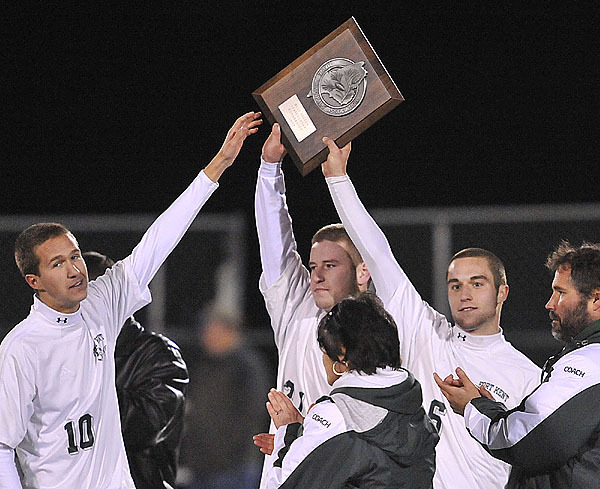 Fort Kent soccer team's Samuel Chasse, (10),  Jared Soucy, (21), and Zach Rioux, (6), heft the Class C runner-up trophy in Hampden, Saturday, Nov. 7, 2009. Bangor Daily NEws/Michael C. York