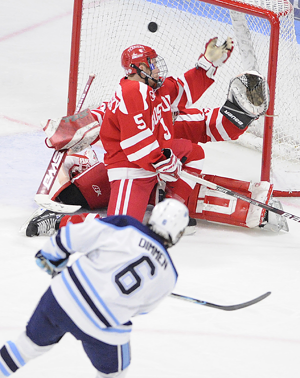University of Maine's Jeff Dimmen puts the puck past Boston University's David Warsofsky (#5) and BU goaltender Kieren Millan, scoring U Maine's first goal in the first period of their hockey match in Orono Sunday aftrnoon, November 8,2009. (Bangor Daily News/John Clarke Russ)