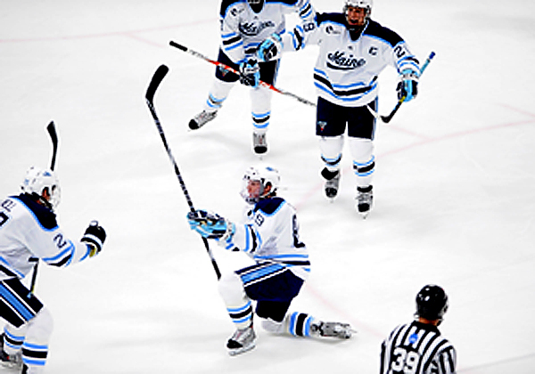 U Maine's Gustav Nyquist (#89) gets down on one knee as teammate Mike Cornell (#2, left), Tanner House (#29, top) and others rush in to congratulate his scoring U Maine's second goal in the first period of their hockey match with Boston University in Orono Sunday aftrnoon, November 8,2009. (Bangor Daily News/John Clarke Russ)