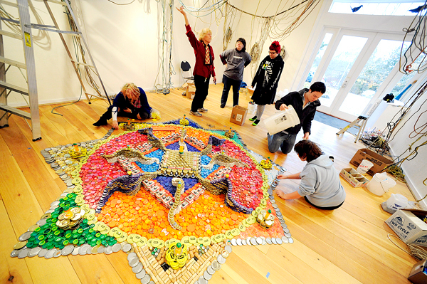 Deer Isle-Stonington high schoolers, under the tutelage of environmental artist Bryant Holsenbeck (pointing) of Durham, NC, continued to assemble a mandala comprised of thousands of bottle caps, can lids and other recyclables at the Haystack Mountain School of Crafts'  Center for Community Programs in Deer Isle Thursday, November 5, 2009.The final result was unveiled Friday, November 6, 2009. (Bangor Daily News/John Clarke Russ)