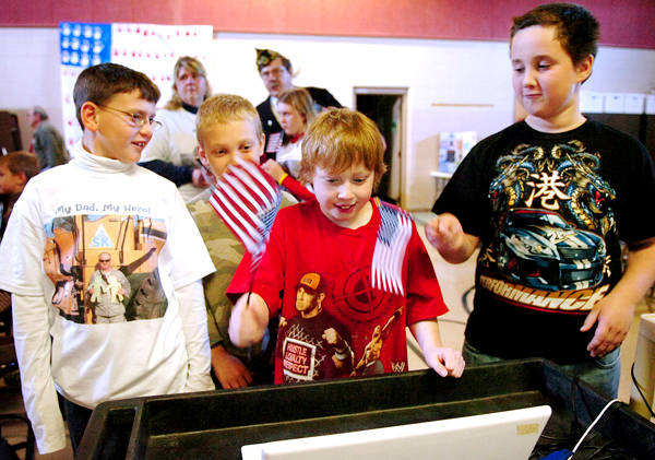 Jake Baker, 8, (from left), Ethan Neal, 10, and Kyle Estes, 10, talk to Jake's father Tech Sgt. Joe Baker and Master Chief Dennis Wellman, who are both currently serving in Iraq, via Skype during a special Veterans Day ceremony at the Marion C. Cook School in Lagrange on Monday, Nov. 9, 2009. BANGOR DAILY NEWS PHOTO BY BRIDGET BROWN