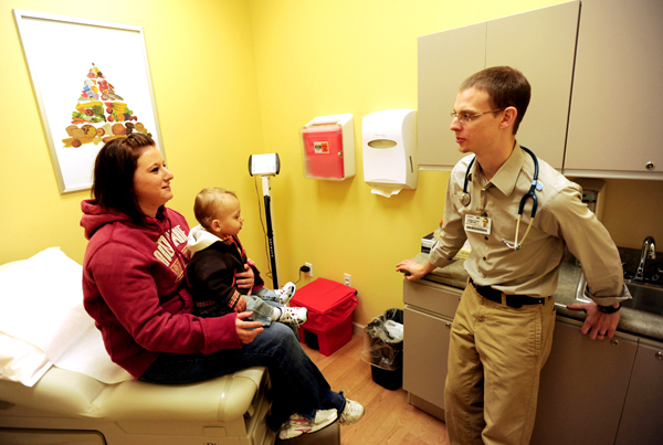 Physicians Assistant Jonathan Campbell, right, talks with patient Megan O'Clair, left, and her son Deklan(CQ) in exam room one at the new  &quotThe Clinic at Walmart&quot on Monday, November 9, 2009. O'Clair was concerned about her sore throat and sought the services of the clinic as it was close to her work place at Dunkin Donuts, which is also located in the Super Walmart on Stillwater in Bangor. BANGOR DAILY NEWS PHOTO BY KEVIN BENNETT