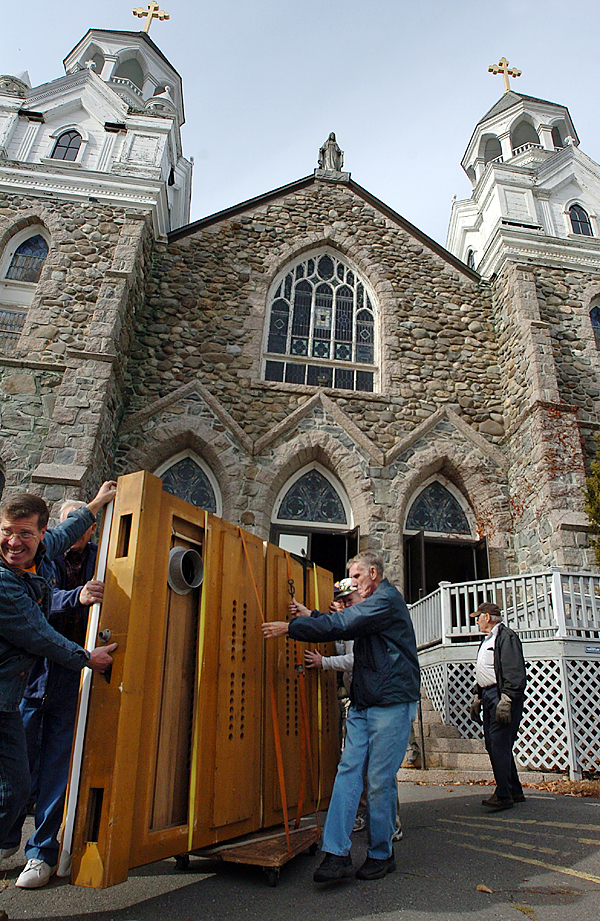 Bob Boutin (far left) and Ron Blair (center) help move the bellows of a 103-year-old Estey pipe organ at St. Mary's Church in Orono on Tuesday, Nov. 10, 2009. Former parishioners, Knights of Columbus members and the David E. Wallace And Company of Gorham, are working this week to move the organ from the now closed St. Mary's Church to the Holy Family Church in Old Town. &quotIt's a gem well worth keeping,&quot said David Wallace of the organ. (Bangor Daily News/Bridget Brown)