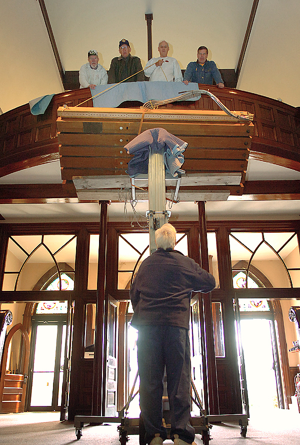 Tom Watson of the Knights of Columbus in Old Town (bottom) along with Grattan Murphy (top, from left), Bob Milheron, Alan Cust and Bob Boutin, help lower the wind chest of a 103-year-old Estey pipe organ at St. Mary's Church in Orono on Tuesday, Nov. 10, 2009. Former parishioners, Knights of Columbus members and the David E. Wallace And Company of Gorham, are working this week to move the organ from the now closed St. Mary's Church to the Holy Family Church in Old Town. &quotIt's a gem well worth keeping,&quot said David Wallace of the organ. (Bangor Daily News/Bridget Brown)