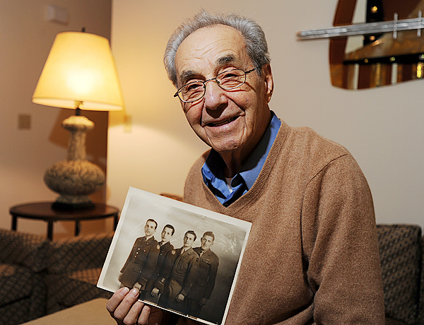 Lester Cohen poses at his Bangor home on Monday, November 9, 2009 with a picture of his three brothers, left to right, Sam, Bernard, Lester and George, in uniform during WWII.  (Bangor Daily News/Kevin Bennett)