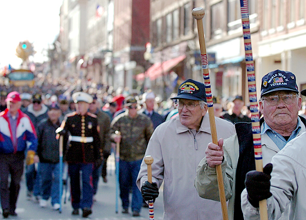 WWII veterans including Al Worster (right) of Carmel, raise their walking sticks to the crowd gathered on Main Street in Bangor during the Veterans Day parade Wednesday, Nov. 11, 2009. (Bangor Daily News/Bridget Brown)