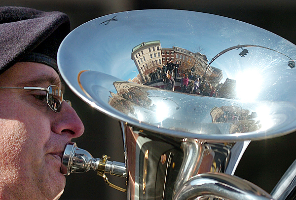 Chris Cook performs with the Maine Army National Guard Band during the Veterans Day parade as a KC-135 tanker (reflected in horn) flies over Main Street in Bangor on Wednesday, Nov. 11, 2009. (Bangor Daily News/Bridget Brown)