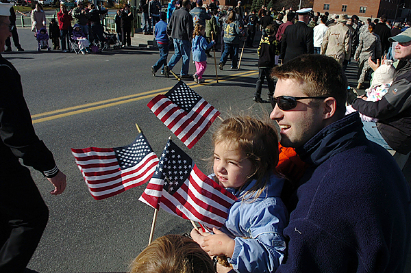 Mark Harvey and his daughter Sylvia, 3, of Winterport wave flags from their perch on the Joshua Chamberlain Bridge in Bangor during the Veterans Day parade Wednesday, Nov. 11, 2009. (Bangor Daily News/Bridget Brown)