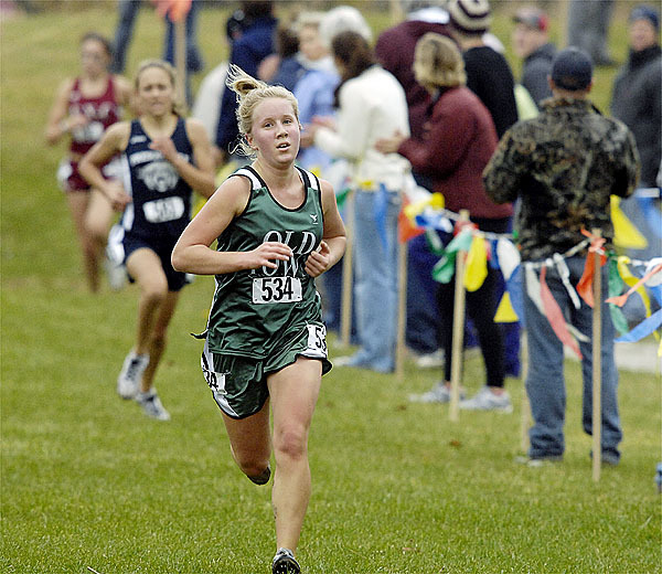 Old Town's Dacie Manion crosses the finish line to win the Eastern Maine Class B cross country race with a time of 20 minutes, 10.05 seconds over the 5k course.  (BANGOR DAILY NEWS PHOTO BY MICHAEL YORK)  CAPTION  Old Town's Dacie Manion crooses the line to win the girl's class B event, Belfast, Maine, Saturday, Oct. 31, 2009. Bangor Daily News/Michael C.York