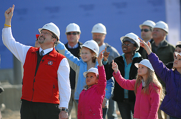 Karl Ward, President and CEO of Nickerson & O'Day, Inc., and Brewer school students from kindergarten through eighth grade, direct the crane operator to raise the last steel beam on future Brewer Elementary-Middle School Campus construction project during Thursday afternoon's ceremony involving the students, Brewer leaders and contractors. (Bangor Daily News/John Clarke Russ