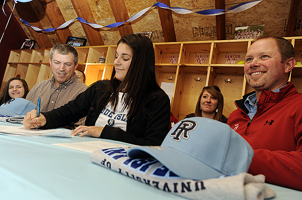 Flanked by assistant coach Doug Whitney, left, and head coach Don Stanhope as well as teammates, Bangor High School softball standout Sam Bedore, center, signs a National Letter of Intent toplay for the University of Rhode Island Rams during Thursday afternoon's press conference in the school's press box.