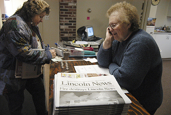 Lincoln News Office Manager Laverne Carll talks on the telephone to newspaper deliveryman Chris DeBeck as an unidentified customer buys a copy of the newspaper Thursday at the Lincoln News' new, temporary offices. (Bangor Daily News photo by Nick Sambides Jr.)