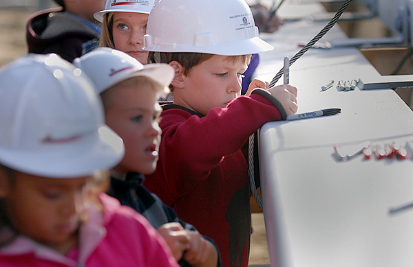 Lucas Beal (center), 7, a Washington Street Elementary School second grader and other Brewer school students from kindergarten through eighth grade, finish signing the last steel beam before it was lifted into place on the future Brewer Elementary-Middle School Campus construction project during Thursday afternoon's ceremony.(Bangor Daily News/John Clarke Russ)