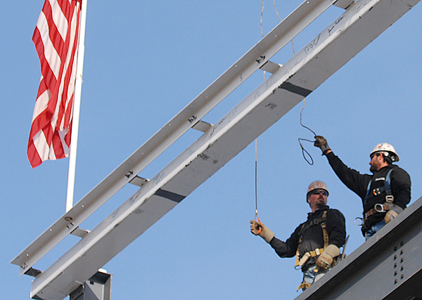 Construction workers help guide the last steel beam atop the future Brewer Elementary-Middle School Campus construction project during Thursday afternoon's ceremony involving the students, Brewer leaders and contractors. (Bangor Daily News/John Clarke Russ)