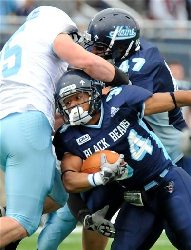 Maine's Rossevelt Boone carries the ball as teammate blocks Troy Russell, (47) Rhode Island's Daniel O'Connell, (25) during the first half of an NCAA college football game in Orono, Maine, Saturday, Nov. 14, 2009. (AP Photo/Michael C. York)