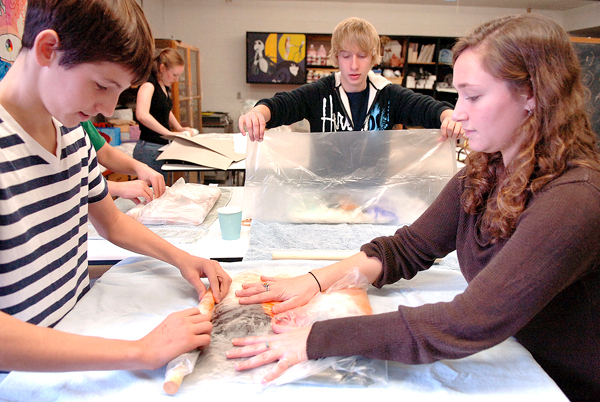 Student teacher Mallory Cudlitz (right) helps Orono High School freshman Schuyler Collett, 14, (left) with his felted wall hanging in a commercial art class Tuesday, Nov. 10, 2009. Cudlitz learned the fiber art from a professor at the University of Maine and has enjoyed passing the technique, which utilizes layers of wool, onto others. Also working on their projects are senior Amber Saucier (back left) and freshman Chad Adams (back right). BANGOR DAILY NEWS PHOTO BY BRIDGET BROWN