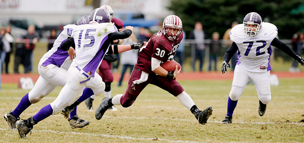 Foxcroft Academy's Ian Champeon (#30) tries to elude John Bapst Memorial High School's Shane Hass (#15), Keith Nelson (#72) and others on a carry in the closing seconds of the first quarter of their Eastern Maine Class C final in Dover-Foxcroft Saturday afternoon, November 14, 2009. BANGOR DAILY NEWS PHOTO BY JOHN CLARKE RUSS