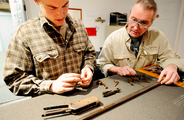 Robin Dietrich (left) and his father Wayne Dietrich look at the parts of a 1908 Winchester a customer sent them to get it refurbished.  &quotThis is about as bad as it gets.&quot said Robin a trained gunsmith as he was taking enventory of the rusted parts of the rifle. &quotI can fix it but it will take a long time probably about a year  until it can be fired.&quot  They opened Diethrich Gunsmithy in Otis five years ago and have plenty of work cleaning, refurbishing and building custom guns for customers in Maine and out of state as well.  BANGOR DAILY NEWS PHOTO BY GABOR DEGRE