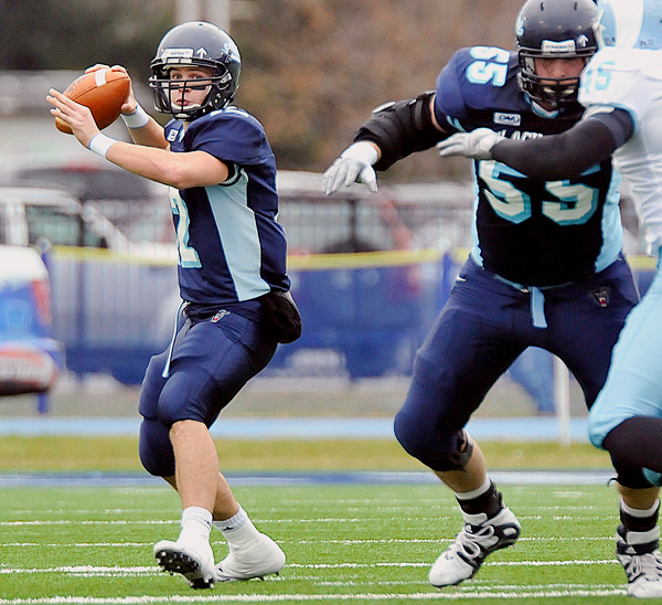 Maine quarterback Chris Treister, (12), looks for a receiver downfiled with pass protection from Matt Barber, (55), in the second half of their NCAA football game in Orono, Maine, Saturday, Nov. 14, 2009. AP PHOTO BY MICHAEL YORK