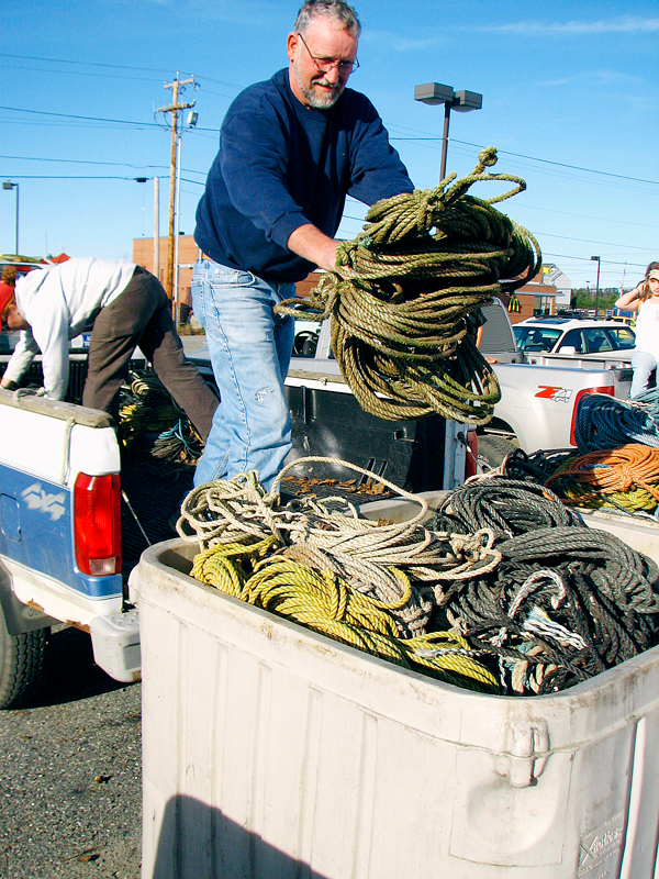 Brent Jones, 61, of Deer Isle, throws float rope form the bed of his pickup truck into a bin at a rope exchange held last week in Ellsworth. Jones said he was trading in about 1,000 pounds of rope for vouchers he can use to buy federally-mandated sinking rope.    BANGOR DAILY NEWS PHOTO BY BILL TROTTER