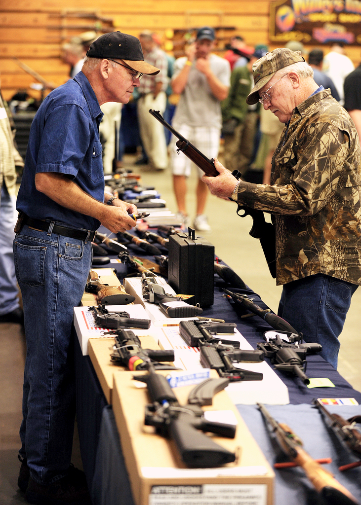 Ivan Smith, right, of Lincoln, inspects a 100 Winchester 308 cal. deer hunting rifle  being offered for sale by Sidney Strom, left,  of Burgess Gun Sales of Bath during the Bangor Gun Show on Saturday, September 12, 2009. Smith said his deer and grouse hunting is &quot just a pastime&quot. BANGOR DAILY NEWS PHOTO BY KEVIN BENNETT