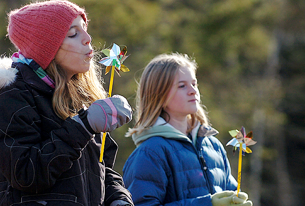 Vinalhaven residents Jessie Creelman, 11, (left) and Hannah Noyes, 11, celebrate the three wind turbines in their community with pinwheels during a ribbon-cutting ceremony Tuesday, Nov. 17, 2009. The trio of turbines are expected to generate enough electricity to power both Vinalhaven and North Haven islands, with excess power being sold back to the regional grid. The venture is the largest community-owned wind project on the East Coast. (Bangor Daily News/Bridget Brown)
