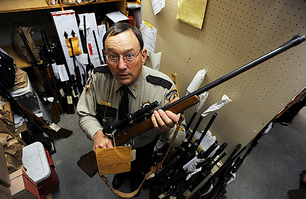 Sheriff Glen Ross poses with one of many guns held in the Penobscot County evidence locker in Bangor on Friday, November 6, 2009. Ross says the guns in lock up are there for various reasons, some were used in a commision of a crime, stolen, found, have missing serial numbers. Others are there for safe keeping while the owners are away or some have been taken away from people who have a restaining order placed on them. (Bangor Daily News/Kevin Bennett)