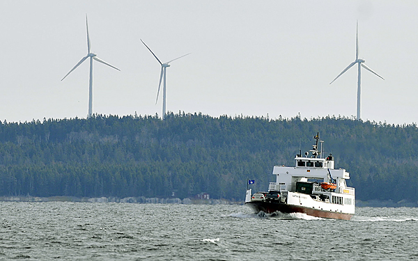 In this Nov. 13, 2009 photo, three recently installed wind turbines loom over a ferry boat returning  from Vinalhaven island in Maine.  The turbines are expected to generate enough power annually to meet the island's demand, with excess power sold into the grid.  The project is regarded as a model for other Maine islands and coastal communities.  (AP Photo/ Portland Press Herald,Gordon Chibroski)