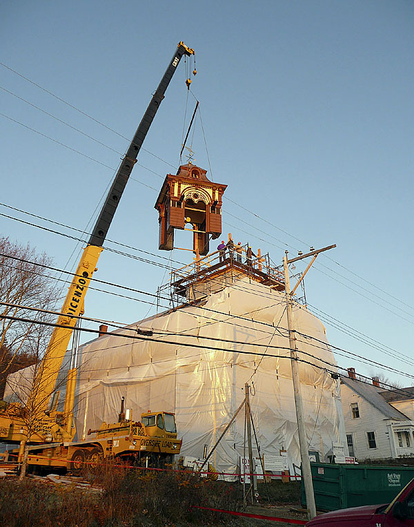 The historic, restored belvedere of the landmark Liberty Hall in Machiasport was raised early Wednesday morning without a hitch. A massive, 60-ton crane lifted the 14,600 pound structure atop the hall, which was once used for town meetings, public suppers and other local gatherings, just as the sun rose over Machias Bay. The belvedere was restored to its original 1873 design by Hewes and Company of Blue Hill and is being installed as part of a larger restoration project by Consigli Construction. A large group of people gathered in the pre-dawn chill to watch the event. &quotI remember bean suppers and town meetings there,'' Douglas Stanhope said as he watched the process. Stanhope grew up in a home next door to Liberty Hall. &quotI used to haul pails of water over for the suppers and get a free meal in return. They would have shooting matches up in back and the winner would get a cake.'' (Bangor Daily News/Sharon Kiley Mack)