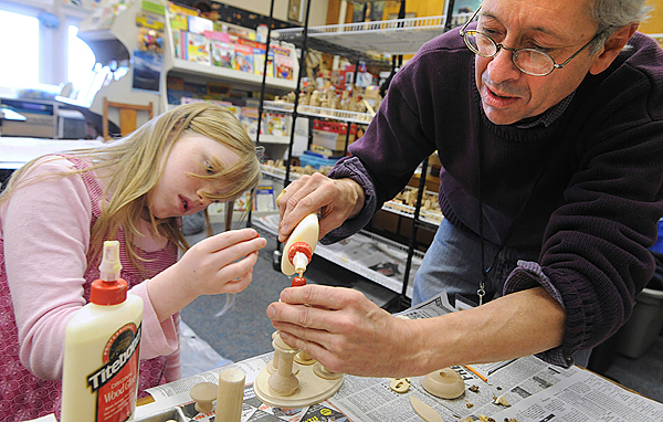 Blake Hendrickson (right) a Brunswick-based artist helps Alexis Parker, 9, glue her design together in the 4th grade class at the Fairmount School in Bangor Tuesday.  Hendrickson is the artist in residence at the school for three days working with 4th and 5th graders on art projects that use scrap wood pieces and wood shavings.  (Bangor Daily News/Gabor Degre)