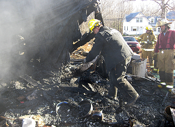 Inspector Ed Archer from the Maine State Fire Marshal?s Office picks through the remains of a house at 157 Pattagumpus Road in Medway on Thursday. The fire has been ruled an arson. PHOTO COURTESY OF MEDWAY FIRE DEPARTMENT