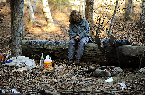 (BANGOR DAILY NEWS PHOTO BY KEVIN BENNETT)  CAPTION  A homeless woman slumps on a log after her male companion passed out while drinking at The Pines on Thursday, November 19, 2009. The Pines is a wooded area near the I-95 Hammond St. exit that is frequented by homeless people who live in make-shift campsites.  It is also the site where Stephen James killed a fellow homeless man, Clyde Worster,  in May of 2008. (Bangor Daily News/Kevin Bennett)