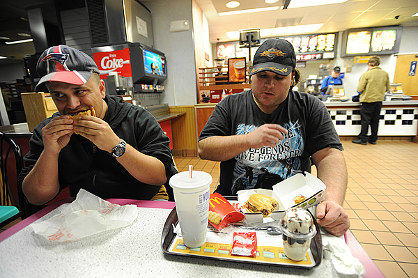 (BANGOR DAILY NEWS PHOTO BY KEVIN BENNETT)  CAPTION  Eric Jutkiewicz, left, of Bangor dines with John Barlow, right, of Bangor at McDonald's on Main Street in Bangor on Wednesday, November 18, 2009. Both live at the Greater Bangor Area Homeless Shelter on Main Street.  Barlow has a job and can dine out when he wants to, but doesn't make enough money to afford his own apartment. Jutkiewicz, who doesn't have a source of income, was given a burger by Barlow. Both have access to hot meals at the shelter. (Bangor Daily News/Kevin Bennett)