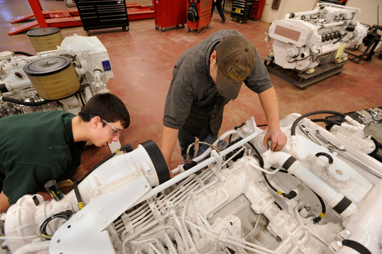 Freshman Jonathan Hallett (left), of Howland, and senior Eric Smith, of Dexter, adjust the rocker arms and valve springs Thursday on one of the diesel marine engines that was recently donated to the automotive department at Eastern Maine Community College in Bangor. Buy Photo