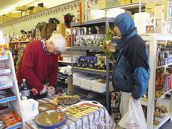 Mike Beals, proprietor of Beal's Variety, hands out Christmas cookies and drinks to customers at his store Sunday afternoon. Downtown businesses in Houlton threw open their doors and slashed prices during the annual Downtown Merchants Holiday Open House on Sunday. Shoppers looking for bargains crowded into Market Square during the event, taking advantage of bargains offered by nearly a dozen businesses. (BANGOR DAILY NEWS PHOTO BY JEN LYNDS)