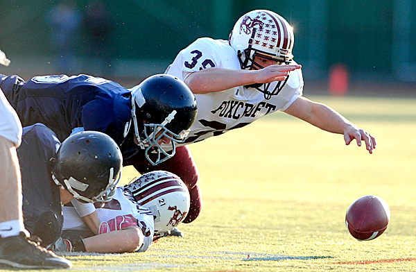 Foxcroft Academy fullback Dylan Andrews (#39) recovers a fumble by teammate Chase Hutchinson as they converge on the loose ball with Dirigo High School players in the first quarter of the Class A State Football Championship at Fitzpatrick Stadium in Portland Saturday, November 21, 2009. The Dirigo Cougars prevailed 37-20. (Bangor Daily News/ John Clarke Russ)