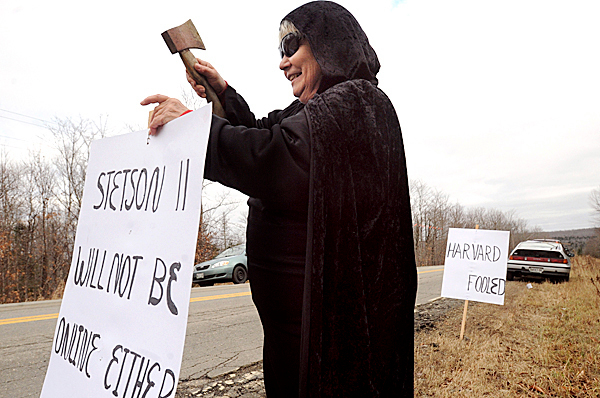 Martha Thacker of Prentiss Township puts up a sign near the entrance to the Steson Wind project expansion Monday.  Thacker was one of the seven people who stood along the road protesting the placing of the turbines in the area.