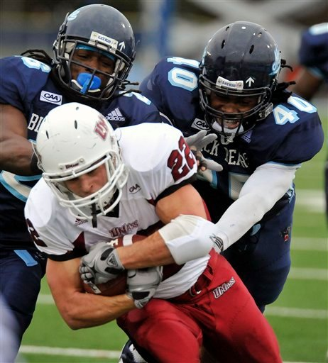Maine's Jerron MvcMillian ,(26), and Vinson Givans,(40), haul down Massachusetts Jonathan Hernandez,(22), on a run  in the first half of their NCAA college football game in Orono, Maine, Saturday, Oct. 31, 2009. (AP Photo/Michael C. York)