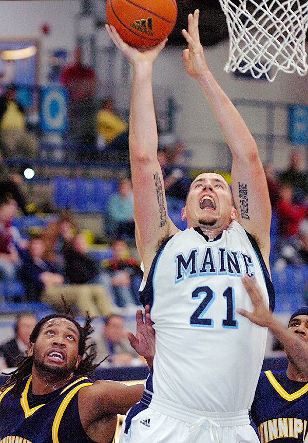 The University of Maine's Sean McNally (21) goes up for a shot against Quinnipiac University's Justin Rutty (lower left), in the first half of Tuesday's game, Nov. 24, 2009 at the Alfond Arena in Orono. (Bangor Daily News/Bridget Brown)