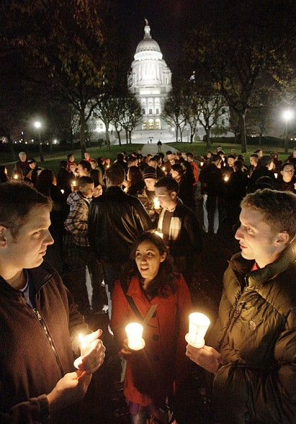 In this photo taken Thursday, Nov. 19, 2009 Drew Grande, of Manchester, N.H., left, Nicole Wilson, of Providence, R.I., center, and Josh Atwood, of Hampden, Maine, right, participate in a candlelight vigil in front of the Statehouse, in Providence. The vigil, sponsored by several groups that support equal rights for same-sex couples, was meant to draw attention to a failed bill that would have given equal rights to same-sex partners following the death of a partner or loved one.  (AP Photo/Steven Senne)