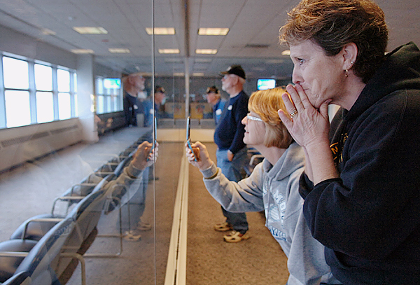 Rhonda Sperrey (center) of Washburn and her sister Sharon Gates of Peru watch as Gates' son-in-law and Sperrey's nephew Cpl. Richard Korhonen, and fellow marines from the 2nd Light Armored Reconnaissance Charlie Company, land at Bangor International Airport after returning from Afghanistan on Thursday, Nov. 26, 2009. &quotI thank the good Lord for all these men,&quot said Sperrey, whose son also serves in the Army. (Bangor Daily News/Bridget Brown)