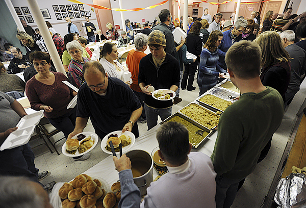 Volunteers fill plates of food and deliver them to seated community members during Manna Ministries thanksgiving day meal on Thursday, November 26, 2009 at the Columbia Street Baptist Church in Bangor. (Bangor Daily News/Kevin Bennett)
