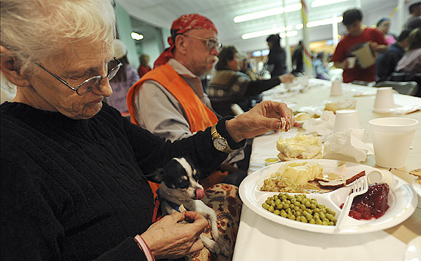 Carolyn McNally, left, feeds her service dog, Princess, while dinning with her friend Frank Nason, second from left, at Manna Ministries thanksgiving day dinner at the Columbia Street Baptist Church in Bangor on Thursday, November 26, 2009. Both McNally and Nason rode together from Lee to attend. (Bangor Daily News/Kevin Bennett)