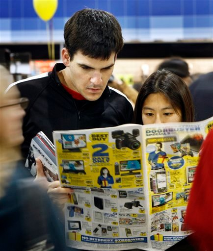 Tom and Vicki Hendrix, of Marblehead, Mass., look through a flyer at Best Buy on Black Friday, Nov. 27, 2009, in South Portland , Maine. (AP Photo/Robert F. Bukaty)