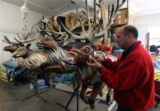 This photo taken Nov. 9, 2009 shows  Macy's Parade Studio Vice President John Piper fixing a sash on one of Santa's Reindeer's while touring the design studio in Hoboken, N.J. (AP Photo/Tim Larsen)