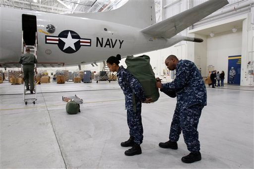 Anthony Bell, right, helps fellow squadron member Laquita Starks, with her pack as she prepares to board the last flight on a P3 Orion, at Brunswick Naval Air Station, Saturday, Nov. 28, 2009, in Brunswick, Maine. The base is relocating its aircraft and personnel to the naval air station in Jacksonville, Fla. (AP Photo/Robert F. Bukaty)