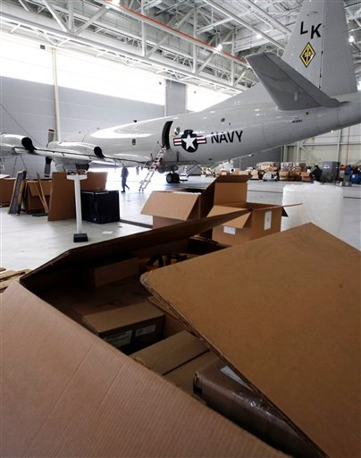 In this Tuesday, Nov. 17, 2009 photo, boxes being prepared for shipment sit near one of the last remaining P-3 Orion planes sitting in a hangar at the Brunswick Naval Air Station in Brunswick, Maine. The last plane is scheduled to leave the base the weekend after Thanksgiving and the entire base is scheduled to be closed in 2011. (AP Photo/Pat Wellenbach)