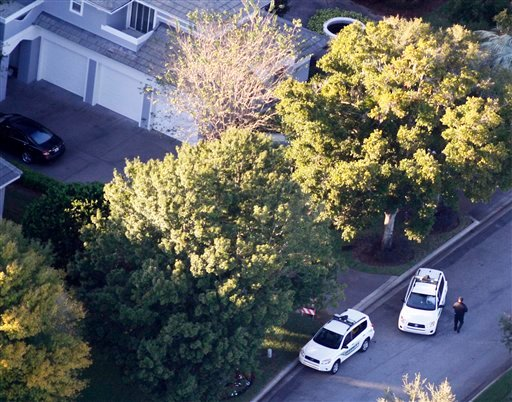 Security guards gather near Tiger Woods' home, left, in Windemere, Fla., Friday, Nov. 27, 2009. Woods sustained facial cuts in a minor car accident early Friday when his SUV hit a fire hydrant and a neighbor's tree as he was leaving his mansion in a gated waterfront community near Orlando, Fla. (AP Photo/Gourav Mukherjee)