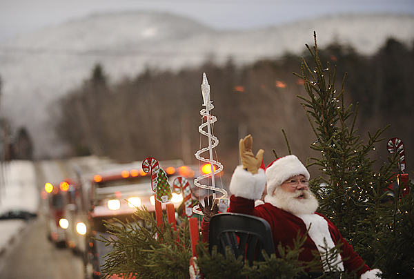 Playing the role of/ Filling in for Santa Claus, Rod Falla of Beaver Cove spreads his holiday cheer on the Moosehead ATV Riders float as the parade moves down Pritham Avenue during the Deck The Halls holiday events in Greenville, Maine Saturday, November 28, 2009. (Bangor Daily News)