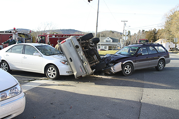 The driver of a GMC pickup (center) was trying to turn left Sunday on Route 17 in Rockport when his vehicle collided with a Subaru (right). The pickup rolled onto its side and came to rest on the hood of a Toyota sedan stopped at the red light on Route 90. Three people were taken to a hospital.